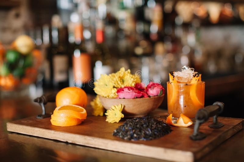 A colorful alcoholic rum cocktail with ingridients such as oranges, tumeric and black sesame seeds. A colorful handcrafted alcoholic rum cocktail with stock image