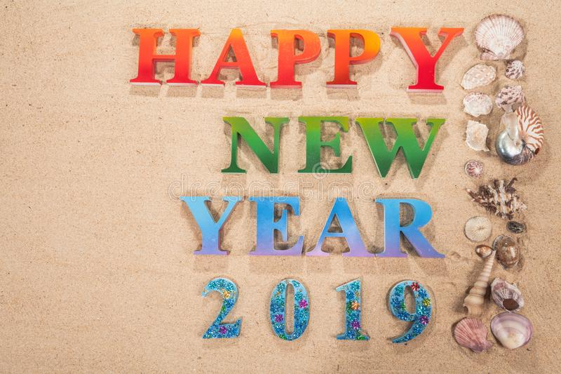 Colorful of alphabet happy new year 2019 on the beach. Decorate with shells with copy space royalty free stock image