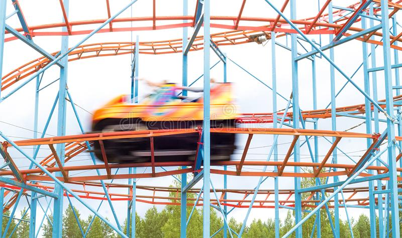 Colorful amusement park ride car going fast by with full speed. People having fun in theme park. Motion blur stock photos