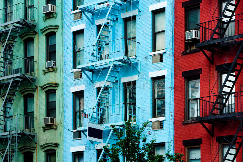 Colorful apartment buildings with fire escapes. Three colorful, red, blue and green, apartment buildings facades with emergency escapes. Typical New York City royalty free stock photography