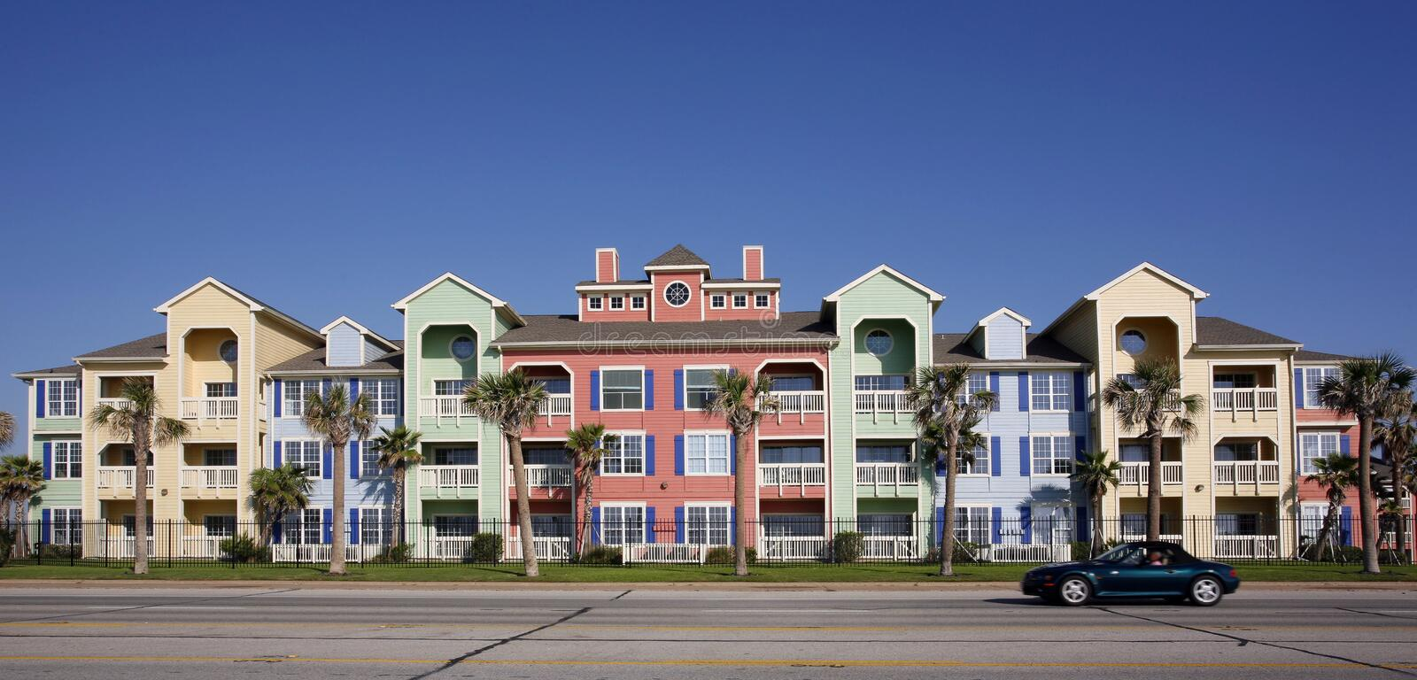 Colorful apartments (condo). Southern style with car running in front on blue sky background royalty free stock image