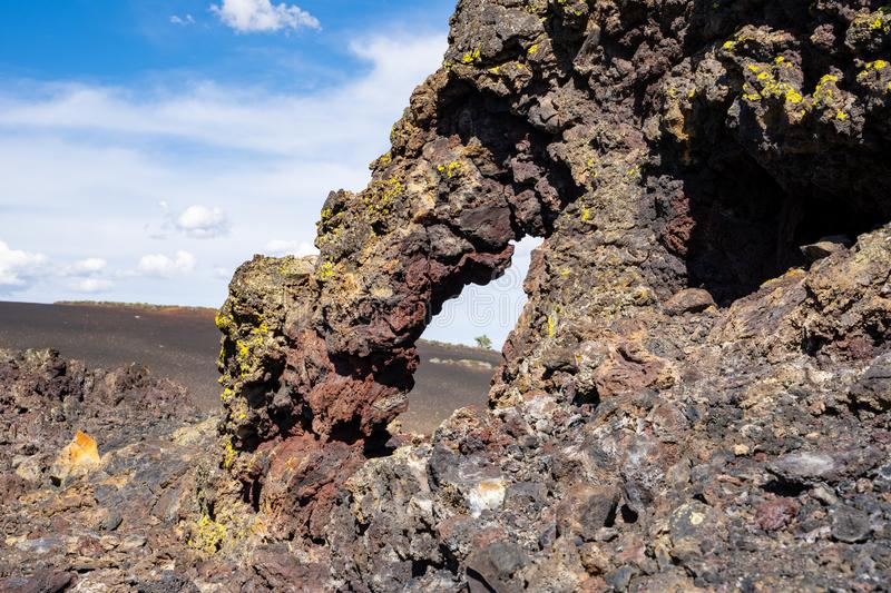 Colorful arch formation in volcanic rock at Craters of the Moon National Monument along Spatter Cones trail royalty free stock photos