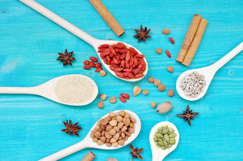 Colorful aromatic condiments seeds and fruits in wooden spoons. Concept of table with colorful aromatic condiments seeds and fruits in wooden spoons, on blue royalty free stock photos