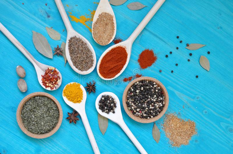 Colorful aromatic condiments spices on blue background.. Concept of table with colorful condiments spices in wooden spoons on blue background, flat lay royalty free stock photo