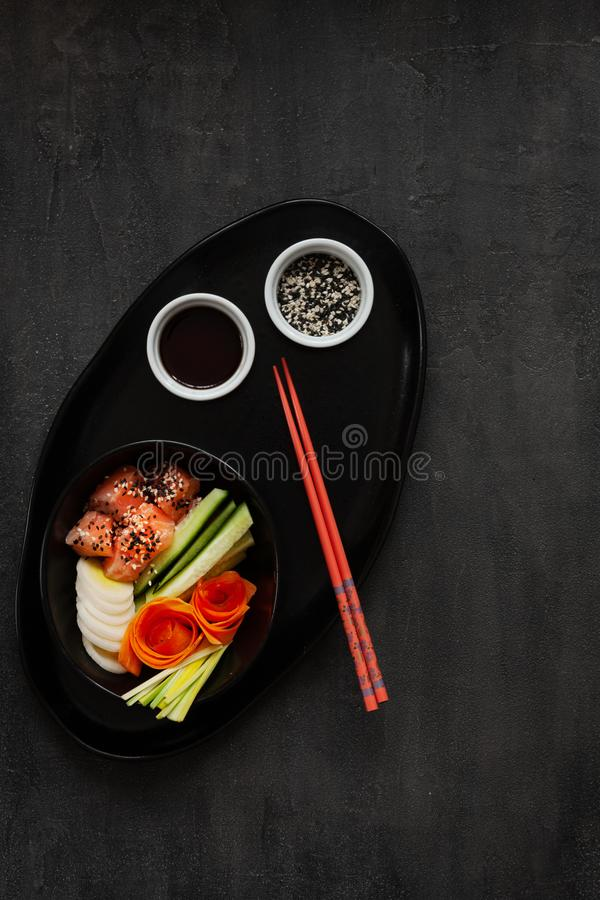 Colorful Asian trendy food, sushi poke bowl with cucumber, salmon, carrot, avocado, Sesame Seeds and soy sauce. Top view, close up royalty free stock photo