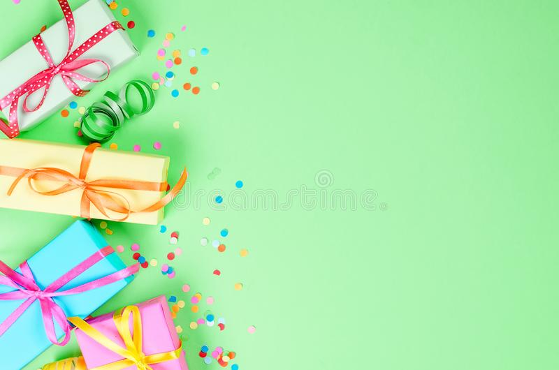 Colorful assorted confetti with serpentine and gift boxes. Colorful Gift boxes, paper confetti and twirled party serpentine on a green background with copy space stock photography