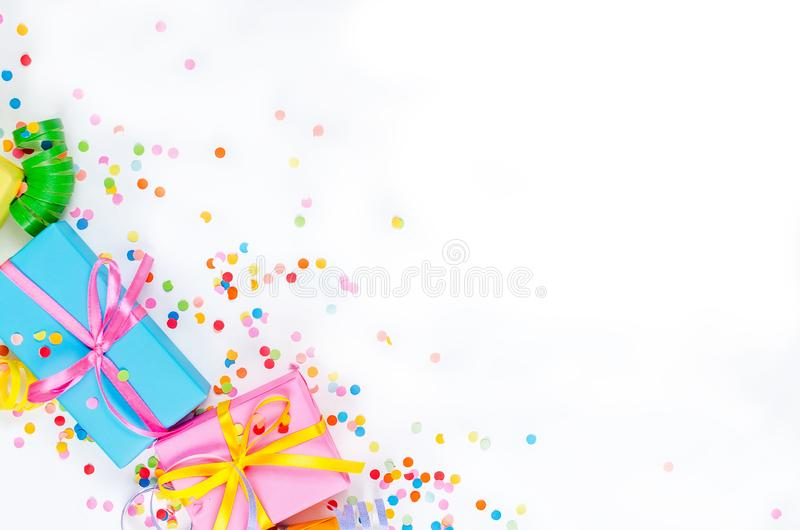 Colorful assorted confetti with serpentine and gift boxes on white. Colorful Gift boxes, paper confetti and twirled party serpentine on a white background with stock photo
