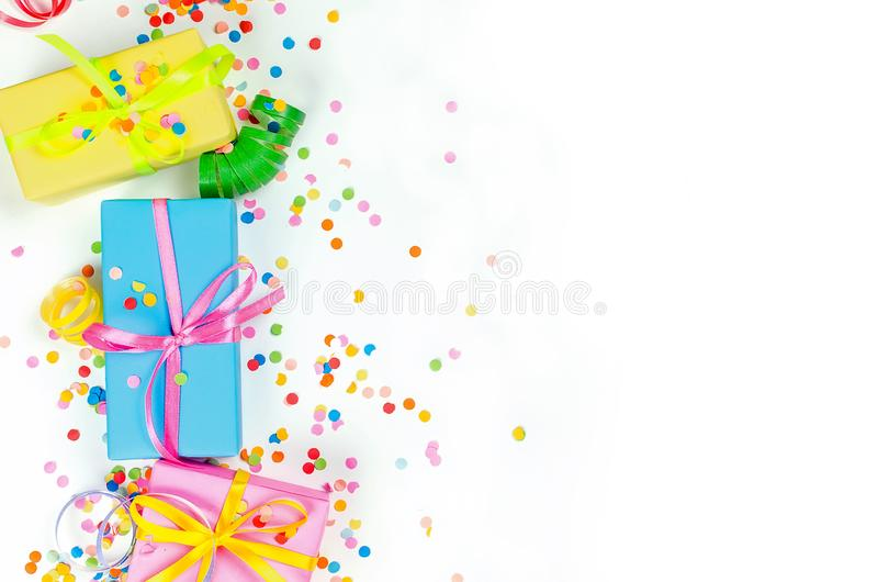 Colorful assorted confetti with serpentine and gift boxes on white. Colorful Gift boxes, paper confetti and twirled party serpentine on a white background with royalty free stock image
