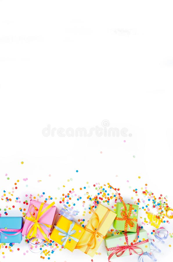 Colorful assorted confetti with serpentine and gift boxes on white. Colorful Gift boxes, paper confetti and twirled party serpentine on a white background with stock images