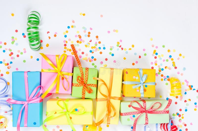Colorful assorted confetti with serpentine and gift boxes on white. Colorful Gift boxes, paper confetti and twirled party serpentine on a white background with royalty free stock photo