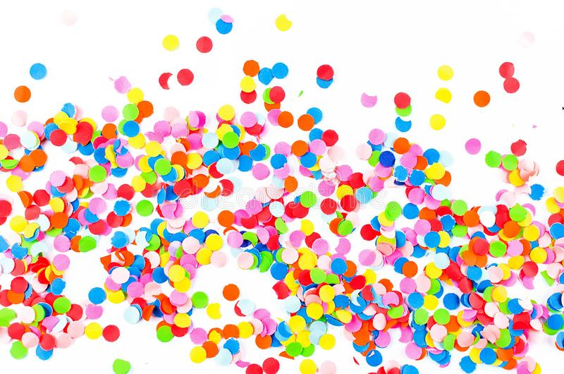 Colorful assorted confetti with serpentine on white. Colorful paper confetti and colored twirled party serpentine on a white background with copyspace in a stock photography