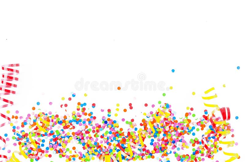 Colorful assorted confetti with serpentine on white. Colorful paper confetti and colored twirled party serpentine on a white background with copyspace in a royalty free stock photo