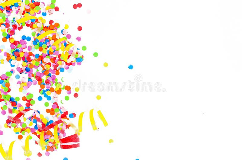 Colorful assorted confetti with serpentine on white. Colorful paper confetti and colored twirled party serpentine on a white background with copyspace in a stock photos