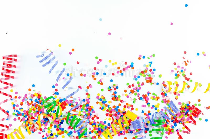 Colorful assorted confetti with serpentine on white. Colorful paper confetti and colored twirled party serpentine on a white background with copyspace in a royalty free stock image