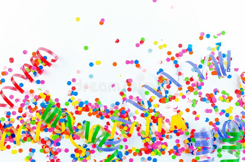 Colorful assorted confetti with serpentine on white. Colorful paper confetti and colored twirled party serpentine on a white background with copyspace in a royalty free stock photography