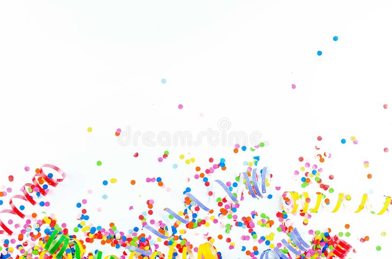 Colorful assorted confetti with serpentine on white. Colorful paper confetti and colored twirled party serpentine on a white background with copyspace in a stock images