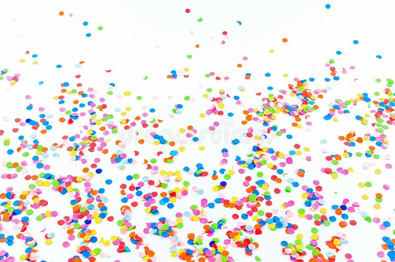 Colorful assorted confetti with serpentine on white. Colorful paper confetti and colored twirled party serpentine on a white background with copyspace in a royalty free stock photos