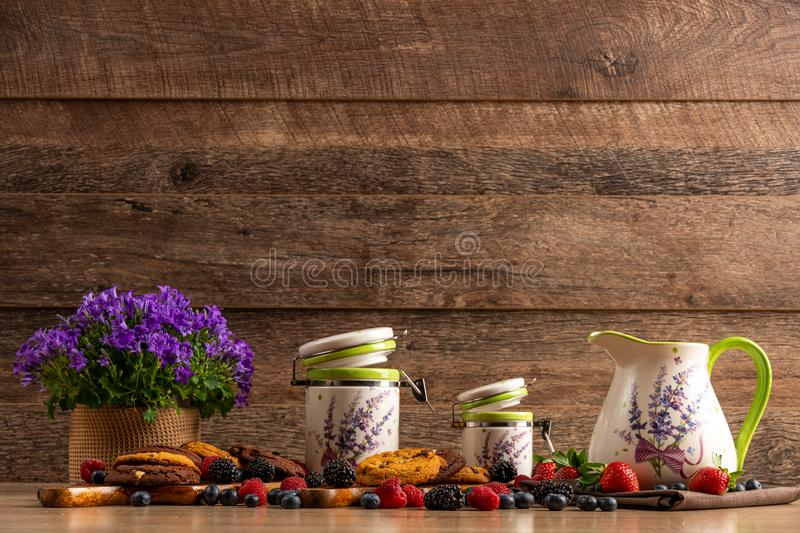 Colorful assorted mix of wild berries, violet flowers, chocolate cookies and ceramic vessels royalty free stock photo