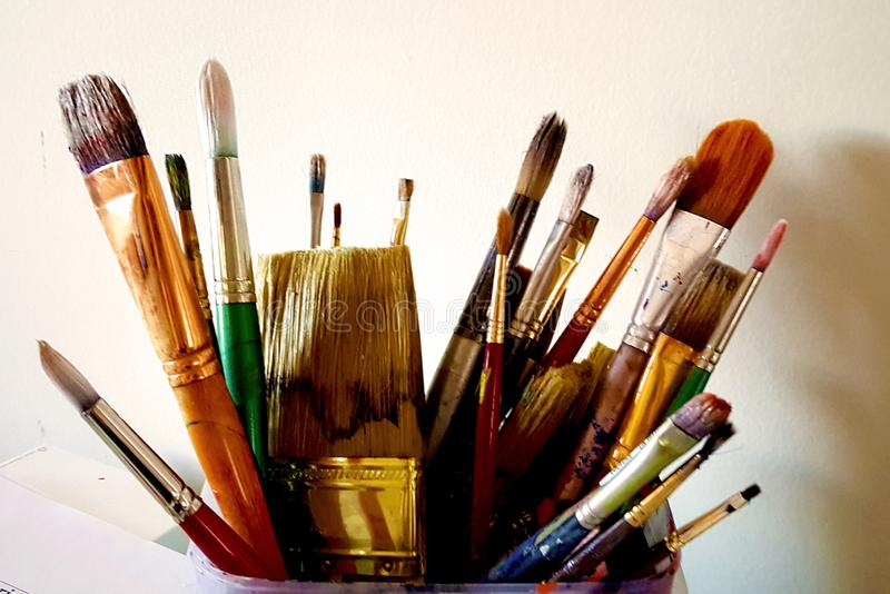 Assorted artist paint brushes for fine art painting. A colorful assortment of used artist's paint brushes in a can. Collection of thick and thin paint stock photos