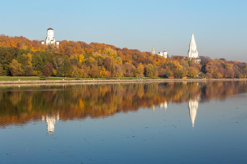 Alley along the riverbank on the background of the autumn park. The ancient domes of Orthodox churches dominate all royalty free stock images