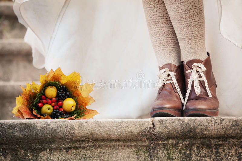 Colorful autumn bouquet and two women legs with le