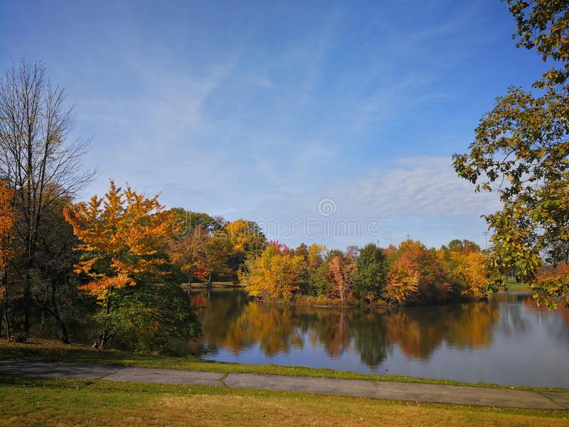 Colorful Autumn forest reflected in calm lake with beautiful white clouds in bright blue sky stock images