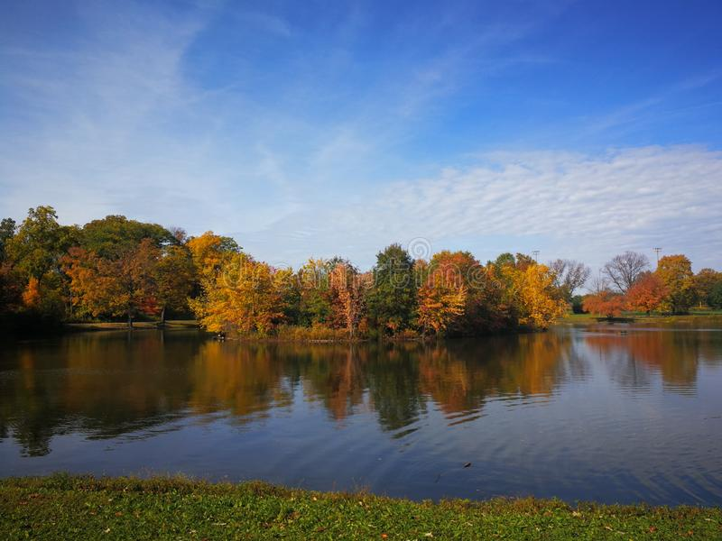 Colorful Autumn forest reflected in calm lake with beautiful white clouds in bright blue sky royalty free stock photography
