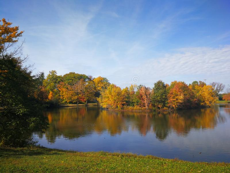 Colorful Autumn forest reflected in calm lake with beautiful white clouds in bright blue sky stock photo