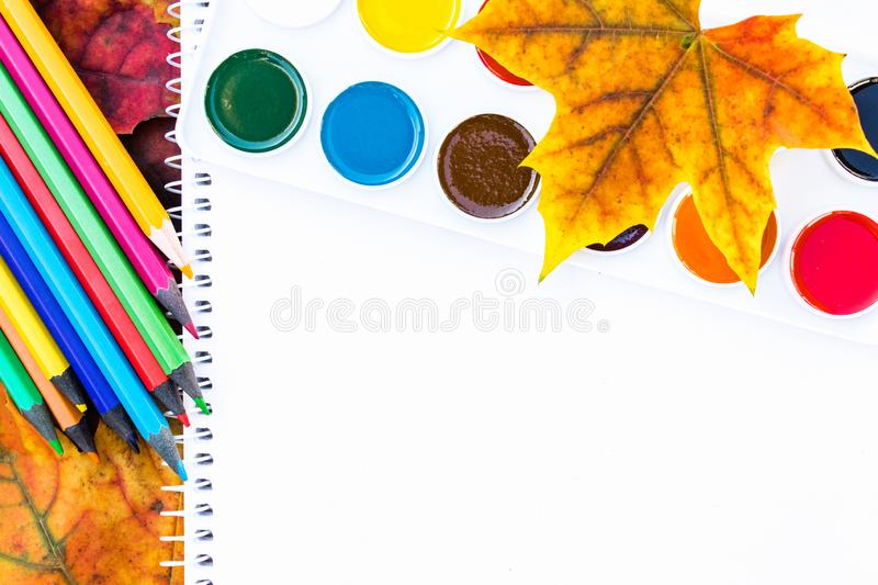 Colorful autumn leaves, multi-colored pencils and paint for painting near white paper with place for text. Background with autumn stock photos
