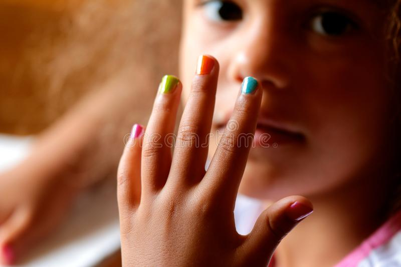 Colorful Baby Nails. Young female child showing off her manicured and colorfully painted finger nails royalty free stock images
