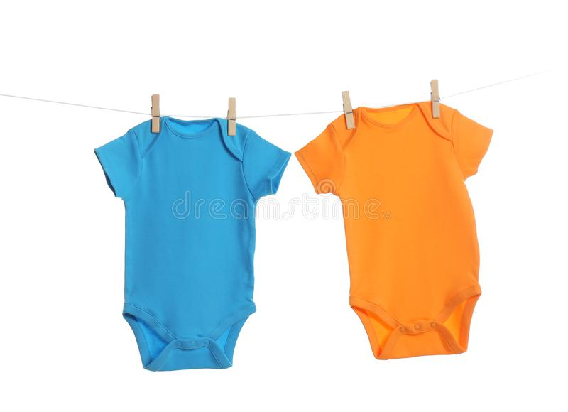 Colorful baby onesies hanging on clothes line. Laundry day stock image
