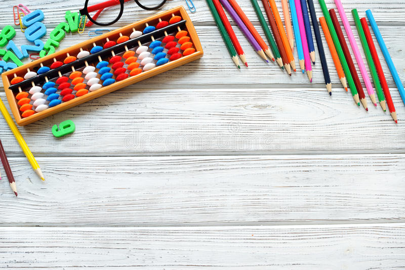 Colorful back to school supplies top border over white table. Mental arithmetic. Space for text. royalty free stock photo