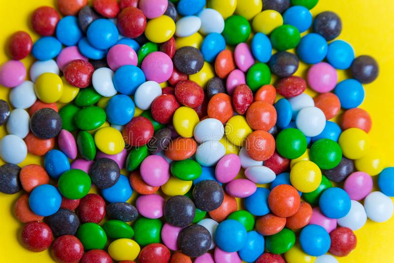 Colorful background of multicolored candy dragees. Round  scattered sweets on a yellow bright background. Happy multicolor texture stock photos
