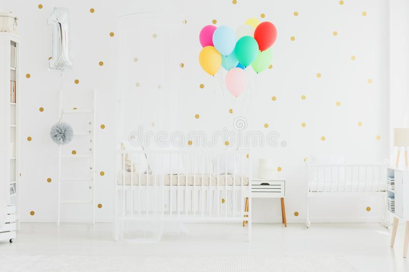 Colorful balloons in baby room. Many colorful balloons in baby room with cupboard standing between white crib and cradle royalty free stock images