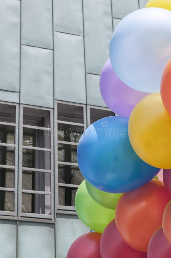 Colourful balloons in the air. Colourful balloons in front of a light blue building with rectangular windows stock photos