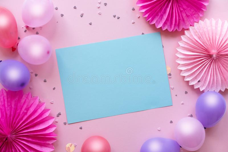 Colorful balloons and confetti on pink table with blue paper in center for text. Birthday, holiday or party background. royalty free stock images