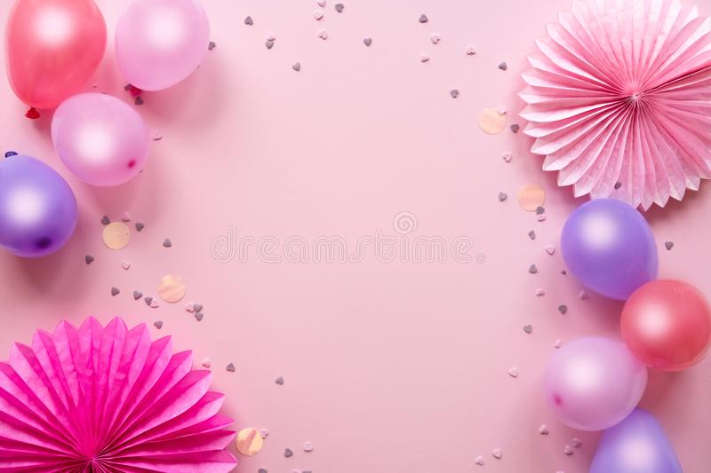 Colorful balloons and confetti on pink table top view. Birthday, holiday or party background. Flat lay style. royalty free stock photos
