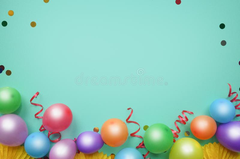 Colorful balloons and confetti on turquoise table top view. Birthday, holiday or party background. Flat lay style. Empty space for stock images