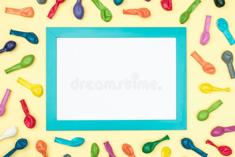 Colorful balloons and frame on colorful background top view. Birthday or party mockup stock photo