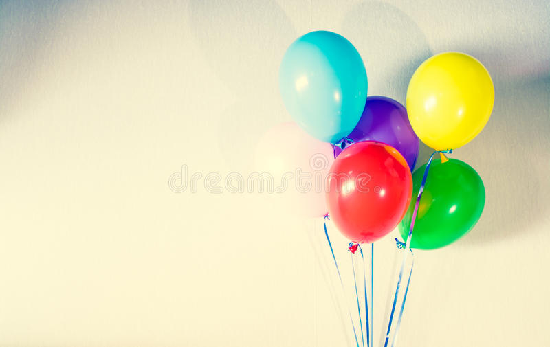 Colorful balloons on grunge wall background. Old vintage style photo. royalty free stock photography