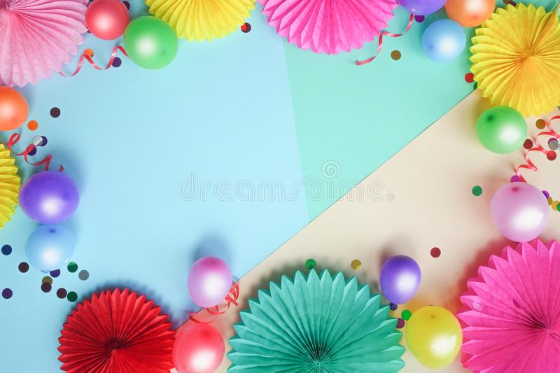 Colorful balloons and paper flowers on blue table top view. Festive or party background. Flat lay style. Copy space for text. Birt stock photography