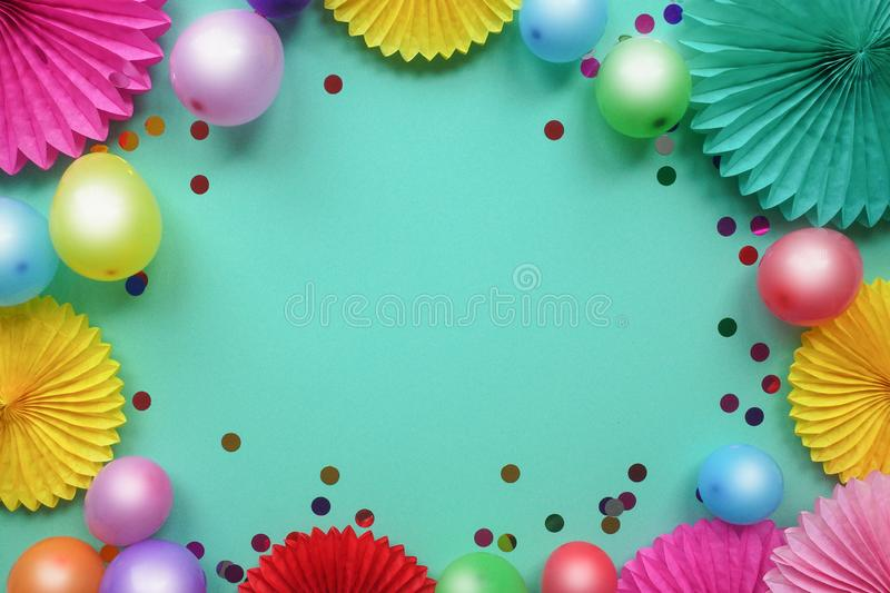 Colorful balloons and paper flowers on blue table top view. Festive or party background. Flat lay style. Copy space for text. Birt royalty free stock photo