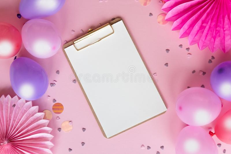 Colorful balloons and paper flowers on pink table top view. Festive or party background. Flat lay style. Copy space for text. stock images