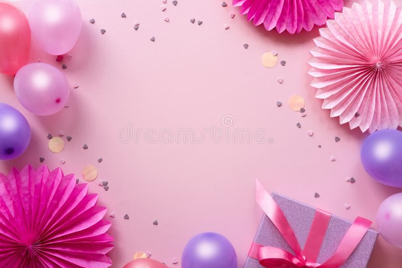 Colorful balloons, present and confetti on pink table top view. Birthday, holiday or party background. Flat lay style. stock image