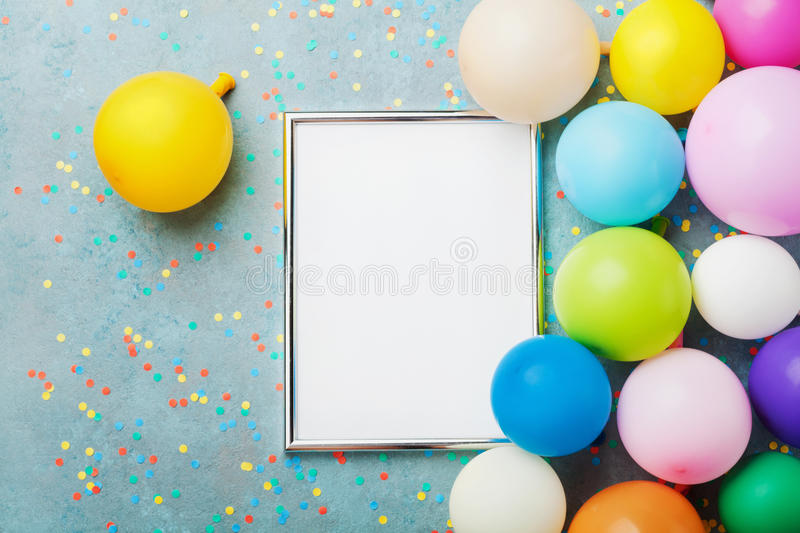 Colorful balloons, silver frame and confetti on blue table top view. Birthday or party mockup for planning. Flat lay style. royalty free stock image