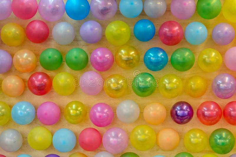 Colorful balloons on a wooden wall stock photo