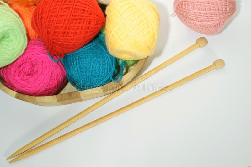 Colorful balls of wool yarn in a decorative basket and wooden knitting needles on the table stock images