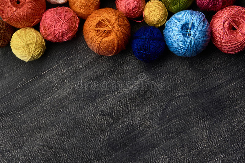 Colorful balls of yarn on wooden background. stock images