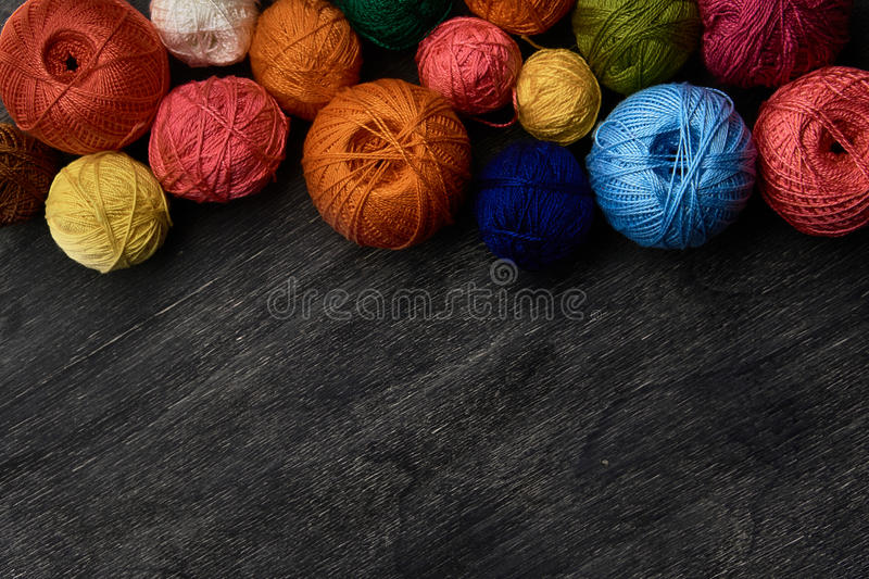 Colorful balls of yarn on wooden background. stock image
