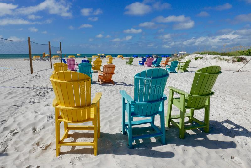 Colorful beach chairs on St. Pete Beach, Florida, USA. Multi colored beach chairs on white sand facing the ocean at St. Pete Beach, Florida, United States royalty free stock photography